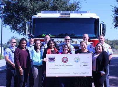group in front of fire truck holding check